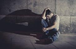 Deprimerat sammanträde för ung man på gatajordning med skugga på betongväggen royaltyfria bilder