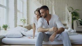 Deprimerat yong mansammanträde i säng som har stressat, medan hans flickvän kommer omfamna honom och kyssa i sovrum hemma arkivfilmer