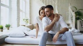 Deprimerat yong mansammanträde i säng som har stressat, medan hans flickvän kommer omfamna honom och kyssa i sovrum hemma Arkivbild