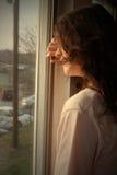 Deprimido mirando hacia fuera la ventana Fotos de archivo libres de regalías