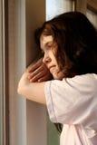 Deprimido mirando hacia fuera la ventana Foto de archivo libre de regalías