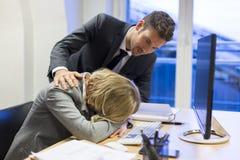 Deprimierende Geschäftsfrau im Büro mit seinem Kollegen Stockfoto