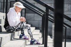 Deprimierende Greisin, die Rest auf Steinstadionsleiter hat Stockfotografie