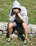 Deprimierender Junge, der ein mit Kapuze Sweatshirt trägt und sein Gesicht bedeckt Lizenzfreie Stockfotografie