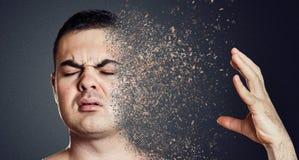 Deprimierender Mann, der sein Gesicht in Stücke auflöst Konzept der psychischen Gesundheit Stockfotos