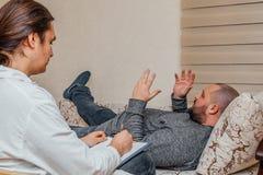 Deprimierender trauriger dicker Mann, der mit Psychologen über seine Probleme spricht Stockbild
