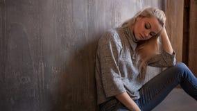 Deprimierendes Mädchen Sitzt auf dem Boden Krise und chronische Ermüdung Junge schöne Blondine in der grauen Strickjacke und in d Stockbild