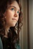 Deprimiert, blaue Augen des Fensters heraus schauend Stockbilder