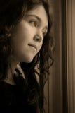 Deprimiert, Fenstergoldaugen heraus schauend Stockfoto