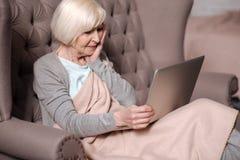 Deprimierte ältere Frau, die Laptop verwendet Stockbilder