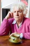 Deprimierte ältere Frau, die am Tisch sitzt Stockfoto