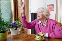 Deprimierte ältere Frau, die am Tisch sitzt Stockfotos