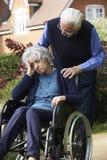 Deprimierte ältere Frau im Rollstuhl, der vom Ehemann gedrückt wird Lizenzfreie Stockfotos