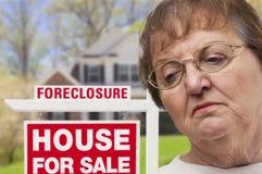 Deprimierte ältere Frau vor Real Estate-Zeichen der gerichtlichen Verfallserklärung Lizenzfreie Stockbilder
