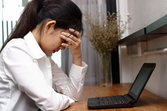 Deprimierte überarbeitete junge asiatische Geschäftsfrau ermüdete von der Arbeit im Büro Stockfoto