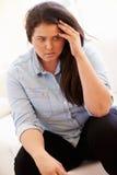Deprimierte überladene Frau, die auf Sofa sitzt Lizenzfreie Stockfotografie