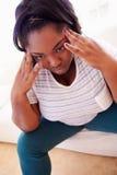 Deprimierte überladene Frau, die auf Sofa sitzt Stockbilder