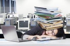 Deprimierte Arbeitnehmerin, die auf Schreibtisch Nickerchen macht Stockfoto