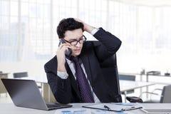 Deprimierte Arbeitskraft, die am Telefon spricht Stockfotos