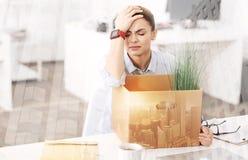 Deprimierte arbeitslose Frau, die im Büro sitzt Stockfoto