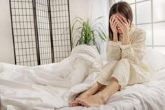 Deprimierte asiatische Frau, die auf Bett sitzt Lizenzfreie Stockbilder