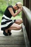 Deprimierte attraktive Blondine auf der Holzbrücke duckend Stockbild