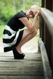 Deprimierte attraktive Blondine auf der Holzbrücke duckend Stockfotos