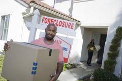 Deprimierte bankrotte Paare, die aus Haus heraus sich bewegen Stockbild