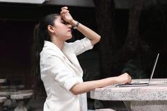 Deprimierte betonte junge asiatische Geschäftsfrau mit dem Laptop, der unter Problem leidet Lizenzfreie Stockfotografie