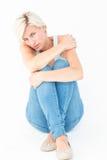 Deprimierte blonde schauende Kamera Stockfoto