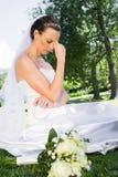 Deprimierte Braut, die im Garten sitzt Stockfotos