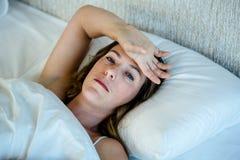 deprimierte Brunettefrau, die im Bett liegt Stockbilder
