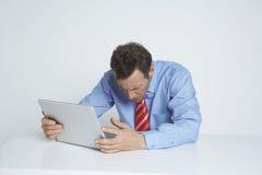 Deprimierte Exekutive, die Laptop verwendet Stockbilder