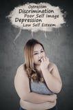 Deprimierte fette Frau, die ihre Probleme denkt Stockfoto