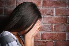 Deprimierte Frau auf Backsteinmauerhintergrund Lizenzfreies Stockfoto