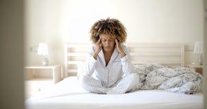 Deprimierte Frau auf dem Bett Stockfoto