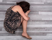 Deprimierte Frau auf dem Boden Stockfotos