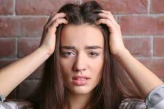 Deprimierte Frau auf Ziegelstein Stockfotografie
