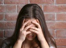 Deprimierte Frau auf Ziegelsteinhintergrund Lizenzfreie Stockfotografie