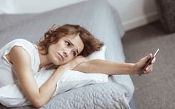 Deprimierte Frau, die auf Bett liegt und Smartphone betrachtet Stockbilder