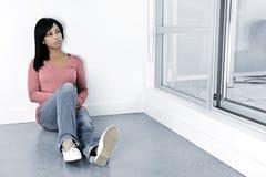 Deprimierte Frau, die auf dem Fußboden sitzt Lizenzfreies Stockbild
