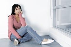 Deprimierte Frau, die auf dem Fußboden sitzt Stockbilder