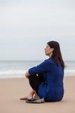 Deprimierte Frau, die auf dem Sand eines Strandes sitzt Lizenzfreies Stockbild