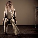 Deprimierte Frau, die auf dem Stuhl sitzt Lizenzfreies Stockfoto