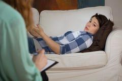 Deprimierte Frau, die auf der Couch liegt Lizenzfreies Stockbild