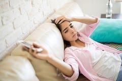 Deprimierte Frau, die auf der Couch liegt Lizenzfreie Stockfotografie