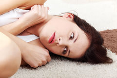 Deprimierte Frau, die auf einem Fußboden liegt. Stockfotos