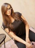 Deprimierte Frau, die auf einem Stuhl sitzt Stockfotografie
