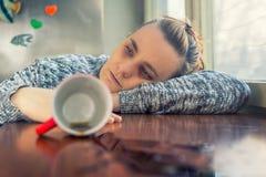 Deprimierte Frau, die auf einen Schreibtisch legt Stockfotografie