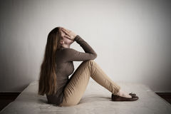 Deprimierte Frau, die auf einer Matratze sitzt Stockfotos